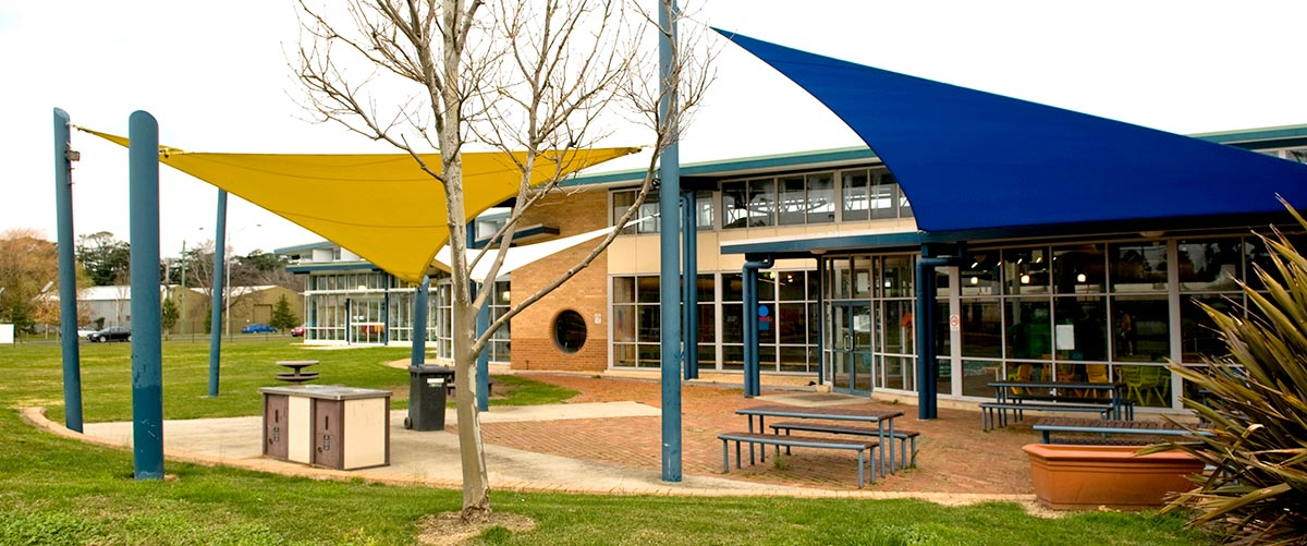 School yard with shade sails over outdoor eating area